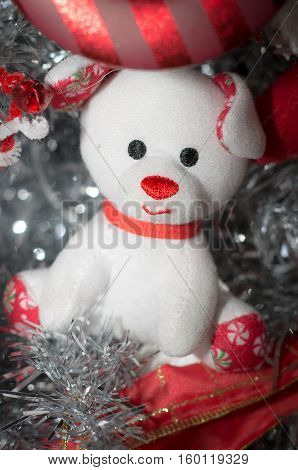 A white stuffed dog in a holiday background