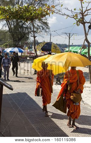 Young Monks With Umbrellas Walking Under The Sun
