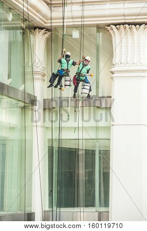 BANGKOK, THAILAND-NOVEMBER 18,2016 :Group of Unidentified Glass cleaner abseiling from a tall building. Window cleaners at work on skyscraper, Bangkok , Middle of Thailand.