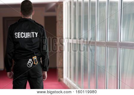 Security man standing back in corridor