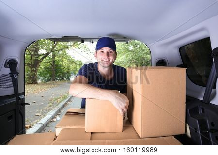 Young male deliverer loading boxes into car
