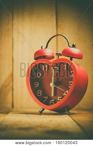 Red alarm clock waking up on wooden background at 6 o'clock