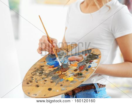 Young female artist with brush and palette in studio, close up view