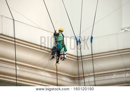 BANGKOK, THAILAND-NOVEMBER 18,2016 :Unidentified Glass cleaner abseiling from a tall building. Window cleaners at work on skyscraper, Bangkok , Middle of Thailand.