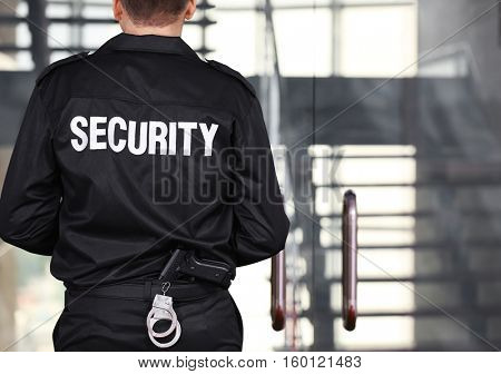 Security man standing back beside stairs