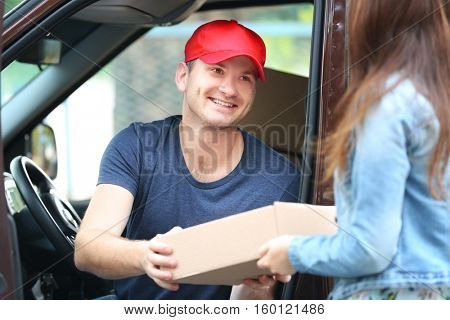 Young male deliverer giving box to woman