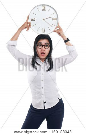 Photo image portrait of a beautiful young Asian businesswoman looked shocked while showing time on clock with both hands holding the clock over her head half body close up portrait over white