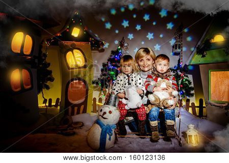 Happy twins with her mother in the fairy town waiting for Christmas presents. Mom with twins sitting in a winter fairy town before Christmas.