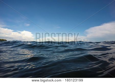 Double landscape water and sky photo. Sea and sky double background. Seaside image. Above and below waterline. White fluffy clouds card. Ocean ripple. Seawater closeup. Banner template with text place