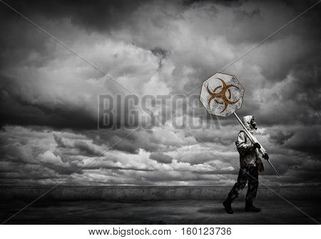 Stalker in gas mask with precaution danger sign
