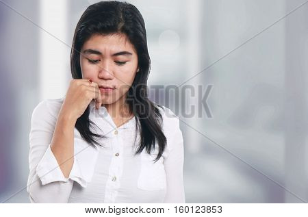 Photo image portrait of a sad young Asian businesswoman looking down while thinking of something half body close up portrait