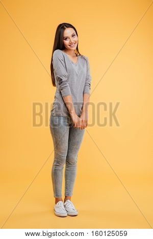 Full length shy woman in studio. isolated orange background