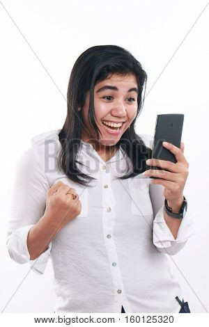 Photo image portrait of a cute young Asian woman looked very happy smiling and exited to get good news on her smart phone. Winning gesture while holding smart phone over white background