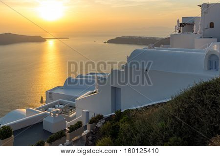 White roof and Amazing sunset in town of Imerovigli, Santorini island, Thira, Cyclades, Greece
