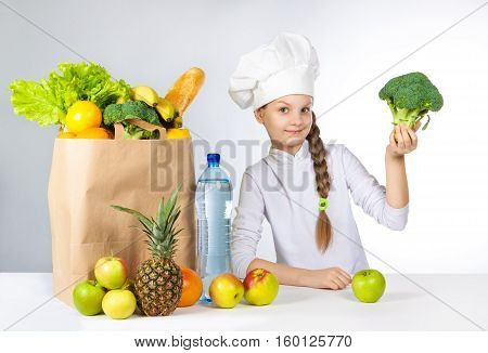 Little Happy Girl In A Cap Cook A Variety Of Fresh Food. Girl Holding Broccoli. And Shows Ok. Positi