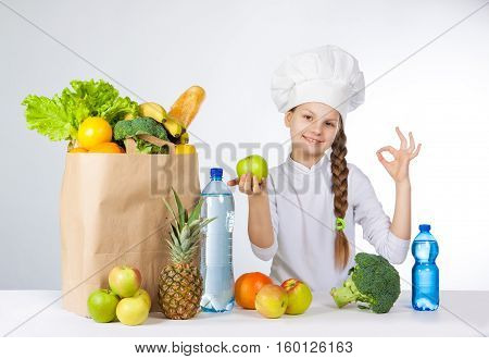 Little Happy Girl In A Cap Cook A Variety Of Fresh Food. Girl Holding A Green Apple. And Shows Ok. P