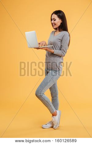 Full length young model stands sideways with laptop in studio. isolated orange background