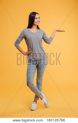 Full length young showing model in studio. girl looking away. arm at hip. Holding invisible copyspace on the pound. isolated orange background