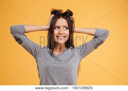 Model in panic in studio. halding her head. looking away. isolated orange background