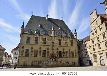Osnabruck, Germany - April 22, 2016. Rathaus building on Markt square in Osnabruck, with people. It was on the steps of this Rathaus that the Peace of Westphalia was proclaimed on 25 October 1648, ending the Thirty-Years War.