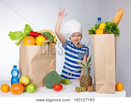 Little Happy Girl In Chef Hat With Big Bags Of Products Held Up Her Hand And Showing Thumbs Up V