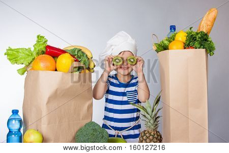 Little Happy Girl In Chef Hat With Big Packages Of Products And Sliced Kiwi Near Eyes