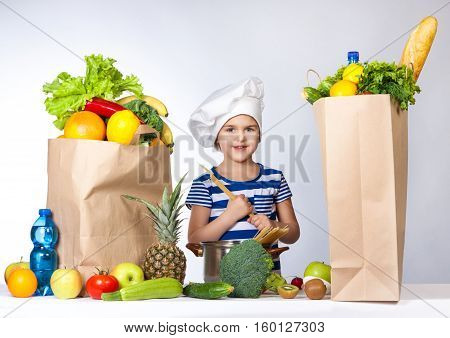 Little Happy Girl In Chef Hat With Big Bags Of Products. It Keeps In The Hands Of Spaghetti