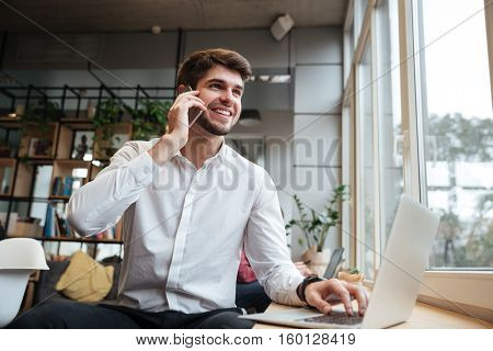 Cheerful businessman dressed in white shirt sitting in cafe and look aside while talking by phone and using laptop
