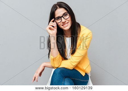 Cheerful young woman wearing eyeglasses and dressed in yellow jacket sitting on stool over grey background while touching eyeglasses and looking at camera.