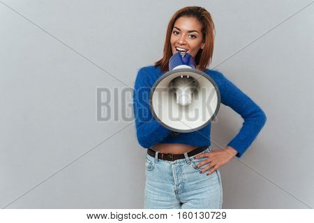 Young pretty african woman in sweater and jeans talking in megaphone and holding one hand at hip. Isolated gray background