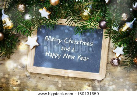 Slate writing board with fir tree branches christmas balls and cookies on a rustic wooden board sample text Merry Christmas and a Happy New Year