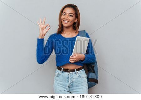 Young smiling african woman in sweater with tablet computer and backpack showing ok sign. Isolated gray background
