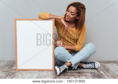 Young smiling african woman in yellow sweater and jeans sitting on the wooden floor and looking at the blank board. Isolated gray background
