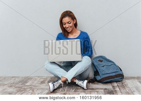 African happy woman in sweater and jeans sitting on the wooden floor in studio with laptop and backpack. Isolated gray background