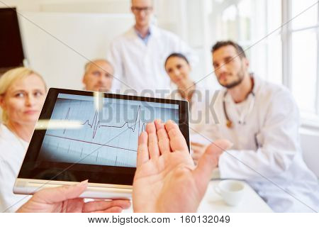 Electrocardiogram on tablet computer and group of doctors talking about ECG