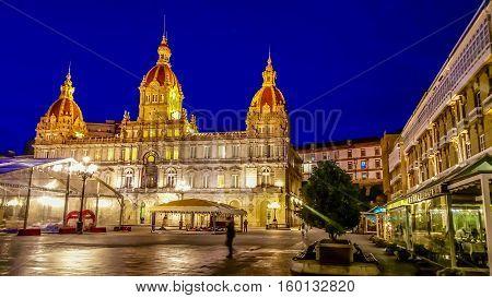 Night cityscape of La Coruna, Galicia, Spain. Illuminated Municipal Palace and City Hall Square of La Coruna at blue evening hour