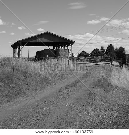 A dirt road leading to a gate and hay storage in Crook county in Central Oregon on a sunny summer atternoon.