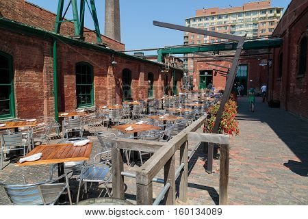 Toronto city, Ontario, Canada, May 22, 2016, Outdoor cafe prepared to serve customers at old vintage Toronto distillery historic district on sunny day