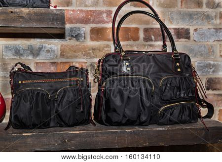 Great amazing fashionable, stylish woman black bags, purse standing on wooden shelf against old brick background