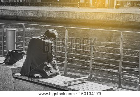 A sad business man is sitting in the public park. Sad and lonely man. Picture in black and white background. Artificial light was added at the top right corner for 'HOPE concept'.