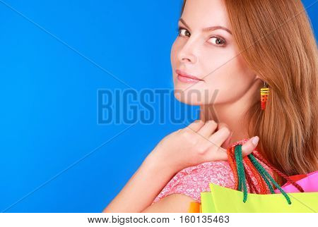 Smiling girl with shopping bags in shop.