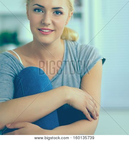 Young beautiful woman sitting on couch at her room .