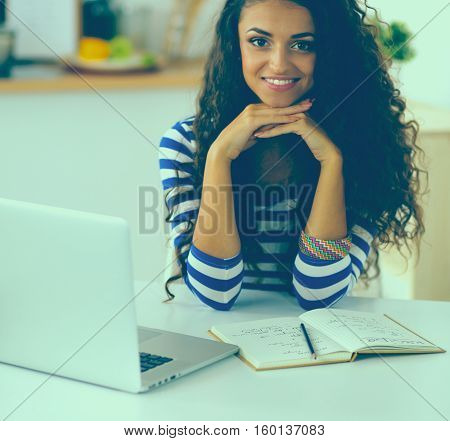 Smiling young woman with coffee cup and laptop in the kitchen at home.