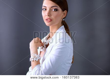 Portrait of pretty young woman with beads, isolated on gray background