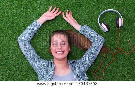 Relaxed woman  lying on the grass near headset .