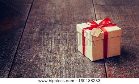 Brown Gift Box And Red Ribbon With Tag On Wood Background With Space. Vintage Gift Box On Wooden Boa