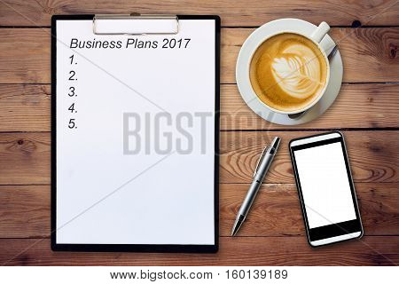 Business Concept - Top View Clipboard Writing Business Plans 2017, Pen, Coffee Cup, And Phone On Woo