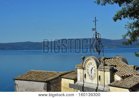 Lake Bracciano viewed from Anguillara Sabazia medieval walls with ancient clock