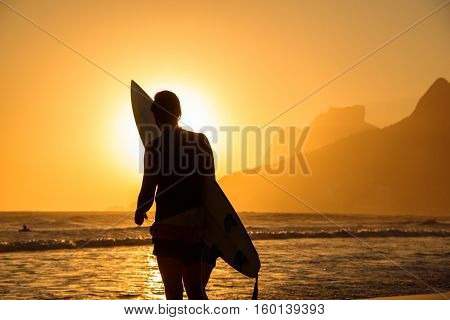 Silhouette of one surfer holding his surfboard on the background of golden sunset on Ipanema Beach and Two Brothers, Dois Irmaos Mountain, Rio de Janeiro, Brazil