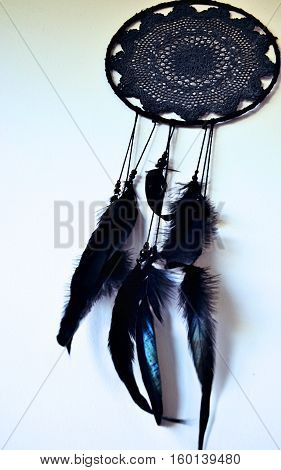 black dreamcatcher hanging on white wall with feathers